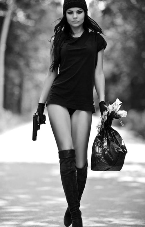 Sexy girl with a pistol and bag of cash - arranging payments